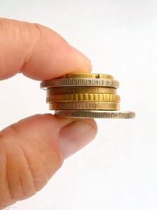 Zwei Finger halten Münzen