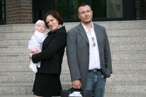 Eltern mit Kind vor Amtsgebäude