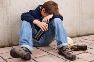 Jugendlicher mit einer Bierflache sitzt auf der Strasse