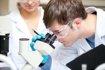 Junger Mann sieht in Mikroskop