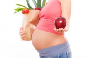Schwangere Frau mit einem Apfel in der Hand