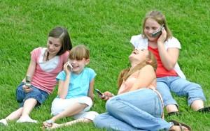 Kinder auf einer Wiese mit Handys