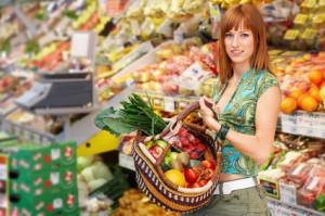 Frau mit Einkaufskorb in Obstabteilung