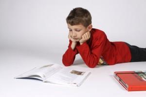 Junge liegt am Bauch und liest ein Buch