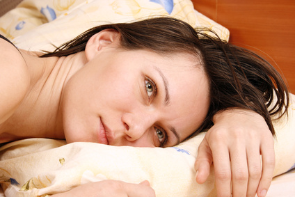 Frau mit besorgtem Gesichtsausdruck liegt im Bett