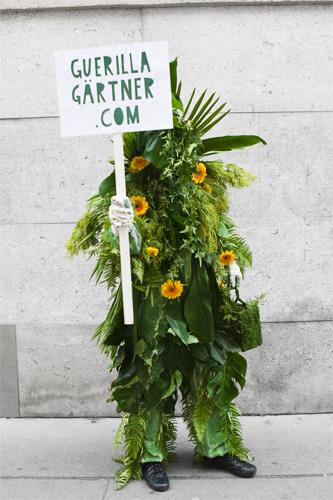 Mit Pflanzen verkleidete Person mit Schild mit Webadresse