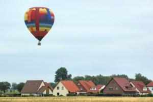Ein Heißluftballon schwebt über Häuserdächern