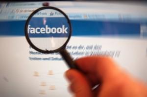 Hand mit Lupe sucht Facebook-Webseite