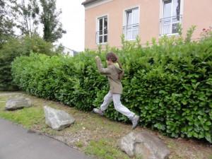 Kind springt über Steine am Linzer Römerberg