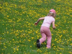 Kind läuft durch die Blumenwiese