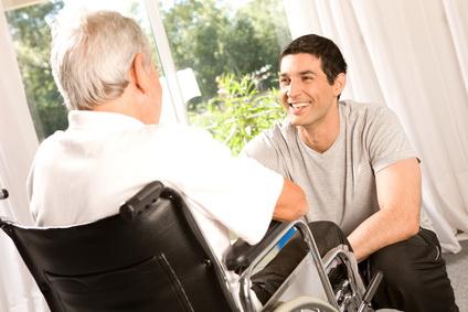 Mann im Rollstuhl unterhält sich mit jungem Mann, der vor ihm sitzt