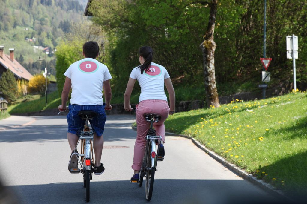 zwei Radfahrer von hinten mit Logo auf Rücken