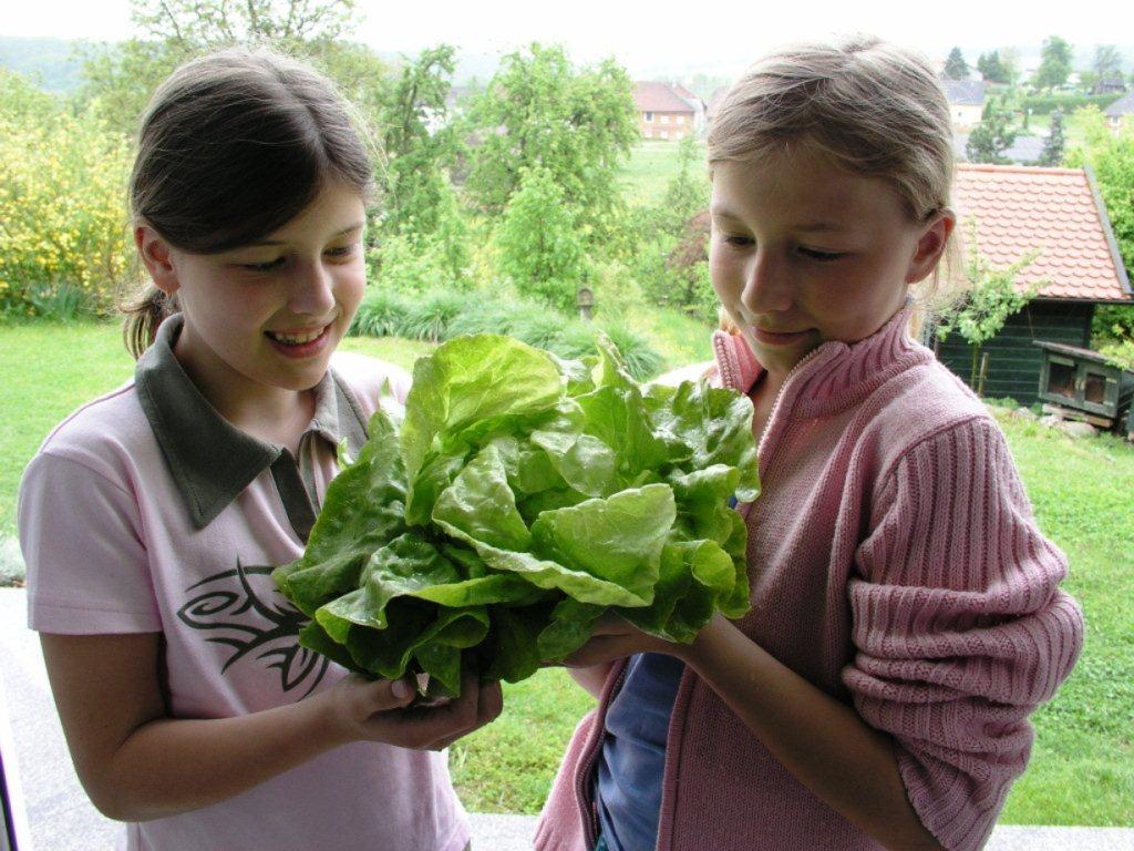 2 <mädchen freuen sich über den frischen Salat