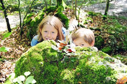 Zwei Kinder schauen hinter einem moosbedeckten Felsen hervor
