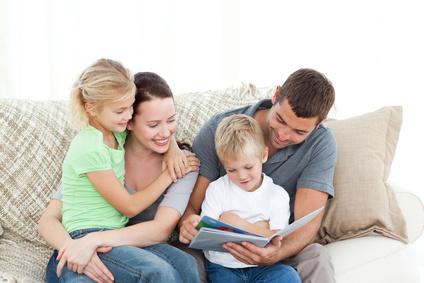 Familie am Sofa liest gemeinsam