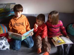 drei Kinder sitzen am Sofa und lesen