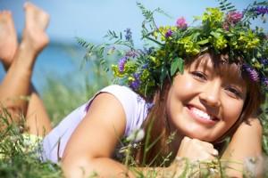 Mädchen mit Blumenkranz liegt in der Wiese