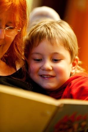 Frau liest Kind aus Buch vor