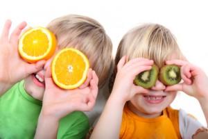 Kinder spielen mit Orangen und Kiwis