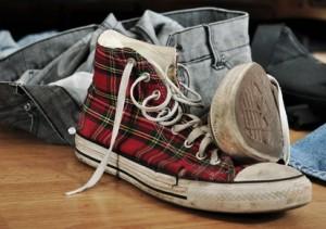 Abgewetzter Turnschuh und Jeans auf dem Boden