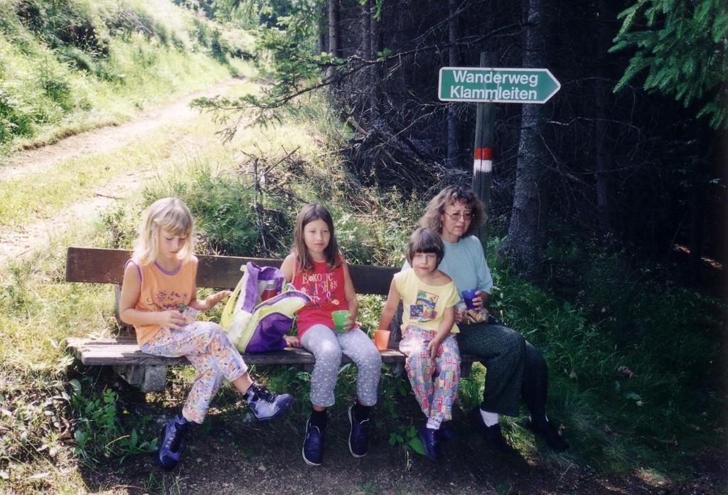 3 Kinder und die Mutter sitzen auf einer bank