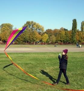 Mädchen auf Wiese lässt Drachen steigen