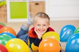 Bild: kleiner junge liegt zwischen luftballons
