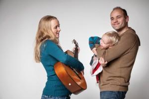 Bild: Frau spielt Gitarre Mann hält Kind am Arm