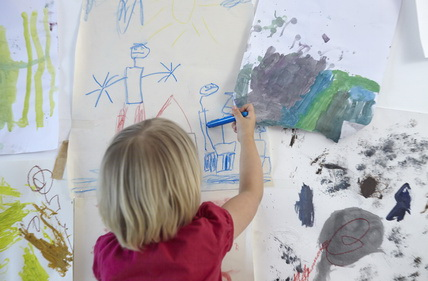 Little girl painting on wall of children's room, rear view