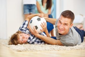 Glücklicher Vater und Junge spielen und toben mit Fußball im Wohnzimmer