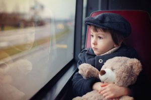 Sweet little child, preschool boy, riding in a bus, daytime, holding teddy bear