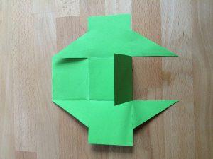 Lege die Figur so vor dich, dass du insgesamt fünf Quadrate hast. Klebe auf das oberste Quadrat ein kleines Stück buntes Papier in einer anderen Farbe (bei mir hier blau). Hier kannst du eine kleine Anleitung hinaufschreiben.